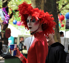 A person wearing a tight red, shiny, long sleeved top and a red feathery hat stands gazing into middle distance holding a Red Bull paper cup. Their face is made up with striking makeup, red lips, blush, blue eyeshadow and thick black eyebrows. The background is that of an outdoor festival, in the sunshine.