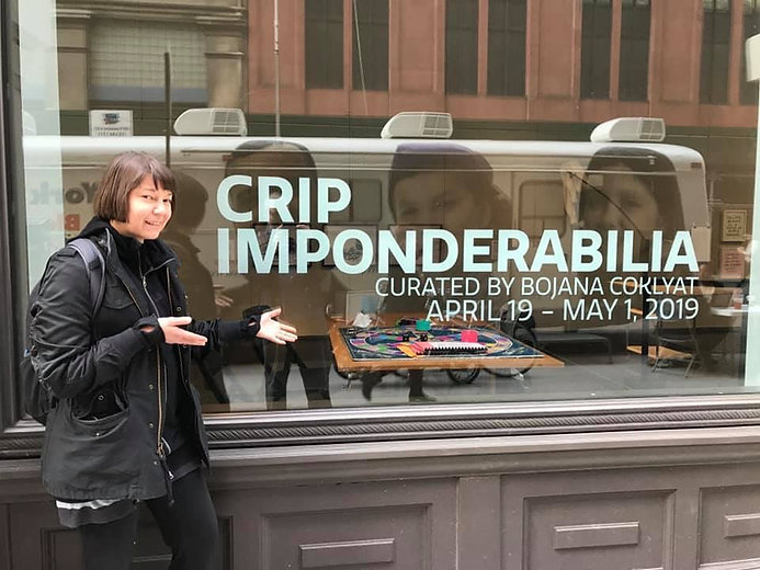 "Bojana, gestures excitedly towards a large window with the title ""Crip Imponderabilia"""