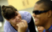 Bojana leans forward smiling broadly at a black teenager who is also smiling wearing sunglasses
