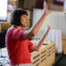 Bojana, a white woman with a brown bob haircut raises her hands in front of her