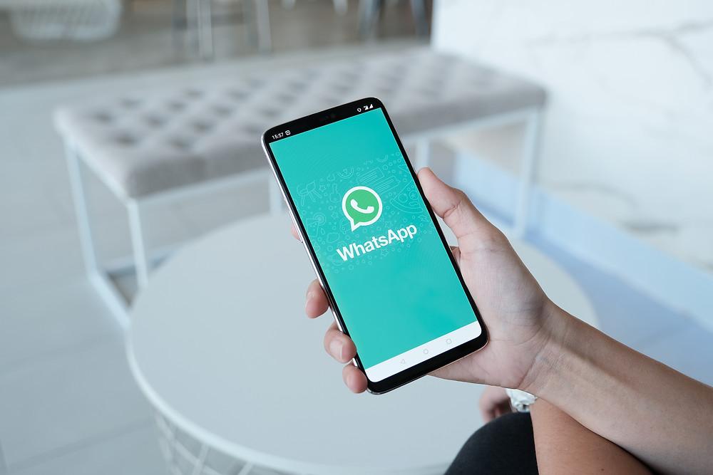 Celular na mão de uma pessoa com aplicativo WhatsApp