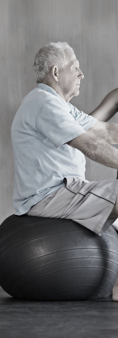 physiotherapist helping senior patient exercise on an exercise ball