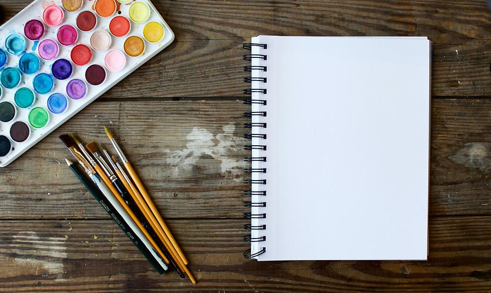 Tim arterbury on unsplash empty sketchbook artist desk brushes and pencils creative space