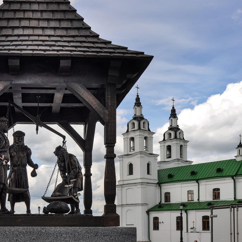 """Памятный знак """"Городские весы"""" на фоне Церкви святого духа."""