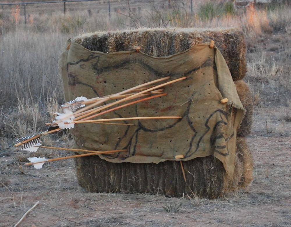 Atlatl darts protruding from hay bales