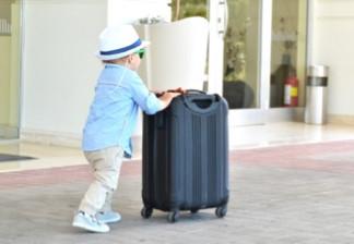 Heavy work child traveling pushing suitcase