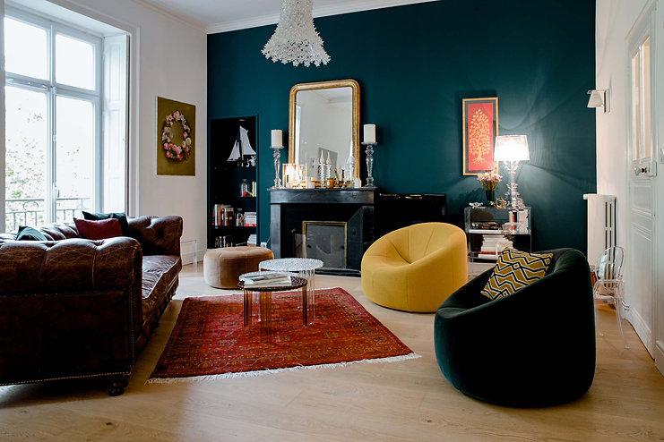 salon chaleur melange moderne et ancien cheminée fauteuils jaunes miroir dore lampe kartell canape cuir club tapis kilim porte bois brut dans couloir moderne agence dekode deco interieur nantes