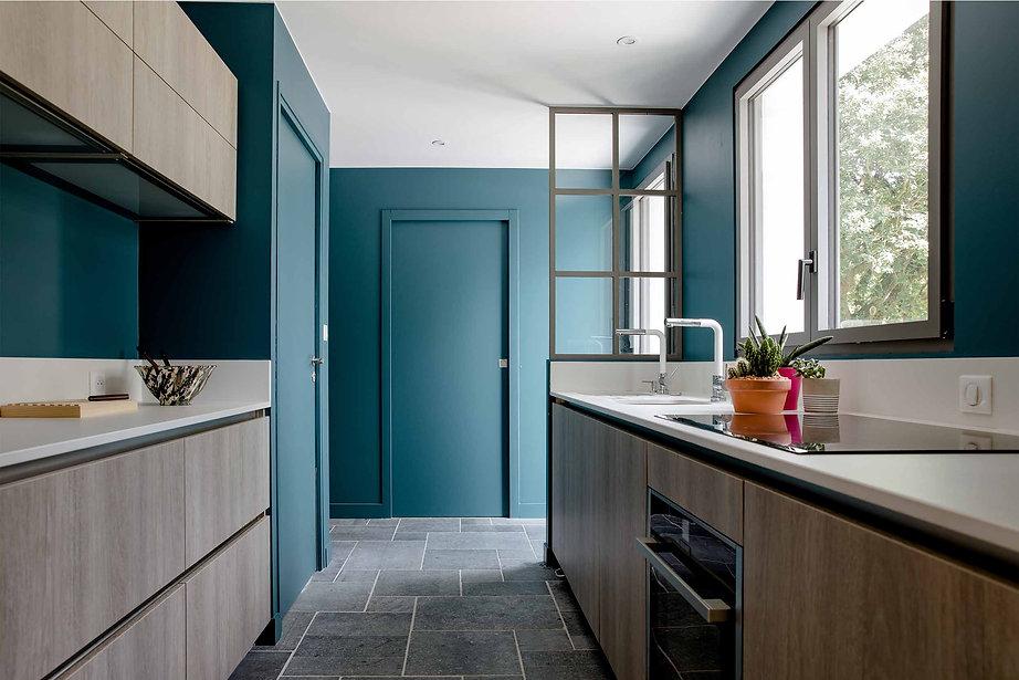 cuisine en couloir bleu canard meubles bois et plan de travail beige verriere grise agence dekode deco interieure nantes