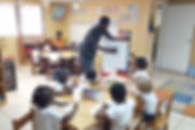 Teacher draws on a whiteboard for his enthralled class of youngsters.