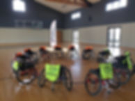 Photo with sports chairs, bibs and flag.