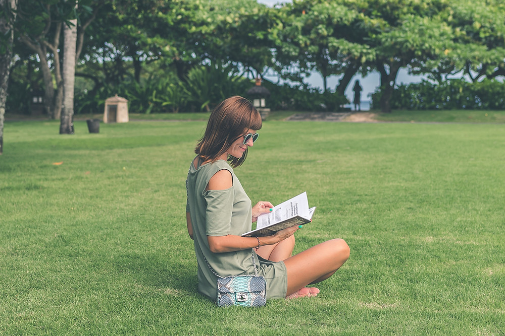 girl sitting on grass with book