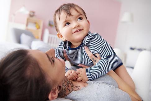 young-mother-cuddling-baby-boy-TTAU4YC.j