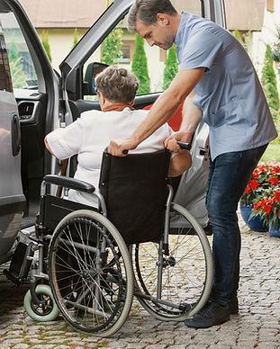 Helpful-male-nurse-with-senior-lady-on-w