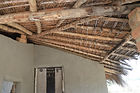 malawi architecture, Roof structure over verandah Mariata village Malawi. Thatch on top of bamboo which is connected to wood poles.