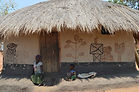 Woman sitting in front of her decorated home Malata village Malawi, malawi architecture