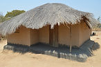Rammed earth home with a covered corner verandah in Nyemba village Malawi. Malawi architecture