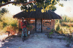 Zambia woman standing in front of her decorated home.jpg