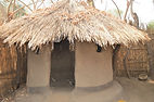 Circular kitchen that is enclosed and has a few small windows. Khisha village Malawi, malawi architecture