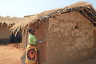 A woman plastering an existing structure in Nkhombe village Malawi. Plastering is done once a year, malawi architecture