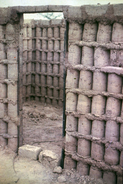 Zambia home being constructed with mud pressed in a paint can with the bottom cu