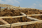 A roof constructed of wood poles constructed into the top of a mud wall in Solola village, Malawi, malawi architecture