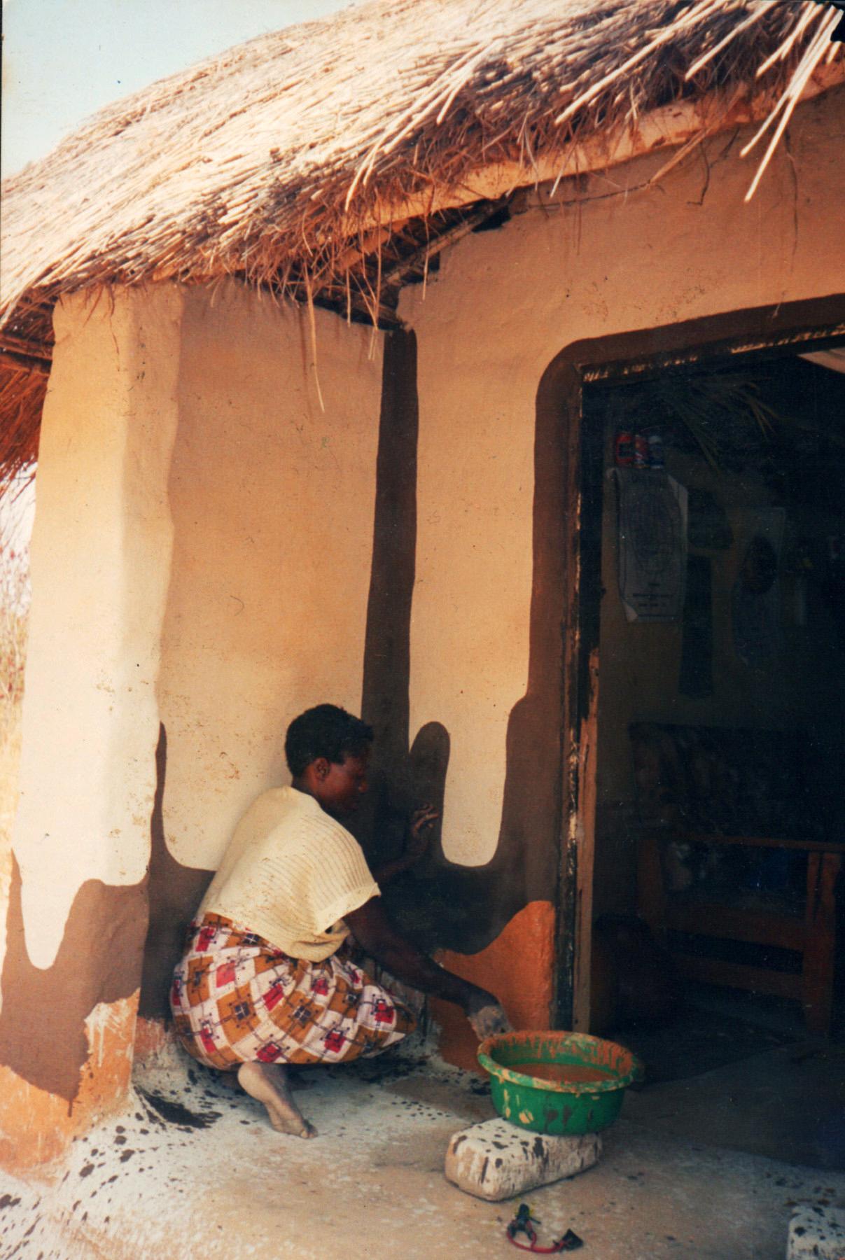 Zambia woman plastering home.jpg