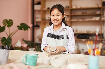 smiling-asian-girl-enjoying-pottery-clas