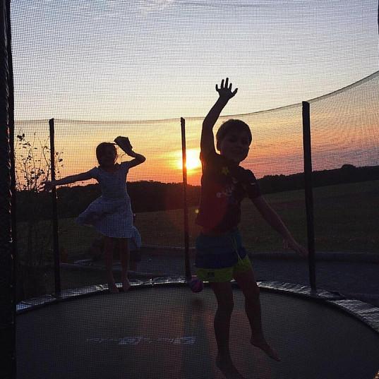 trampoline spingen bij zonsondergang bij