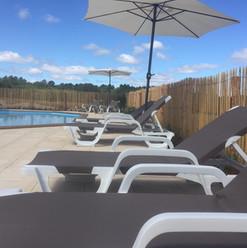 Gedeeld zwembad met ligbedden en parasol