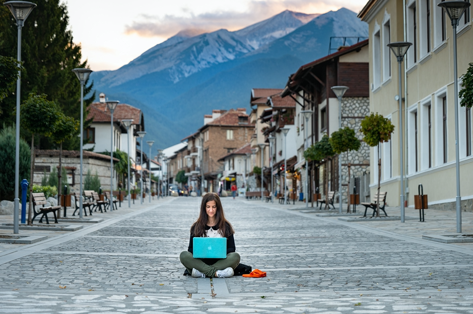 Girl sits cross-legged in the middle of a cobblestone street in a European city on her laptop.