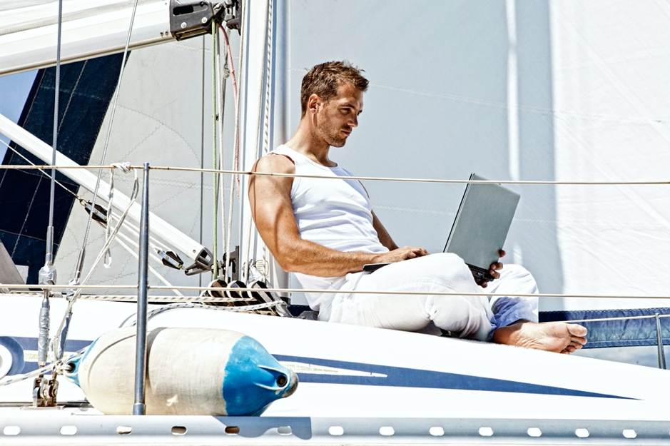 Man dressed in white sits at the front of a sailboat, on laptop.