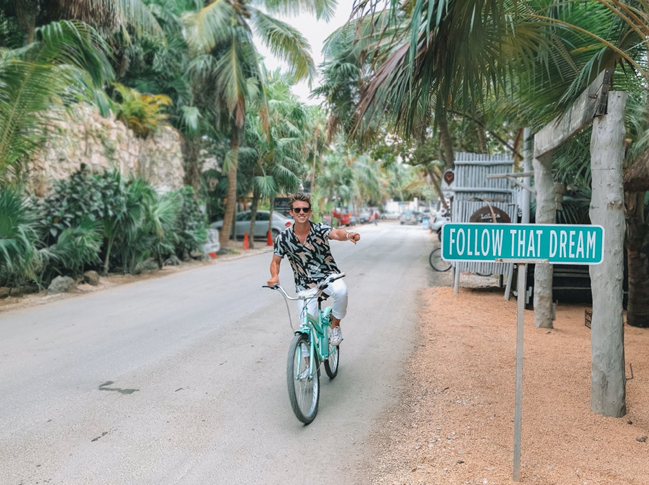 Guy in a tropical location on a bike, smiling.