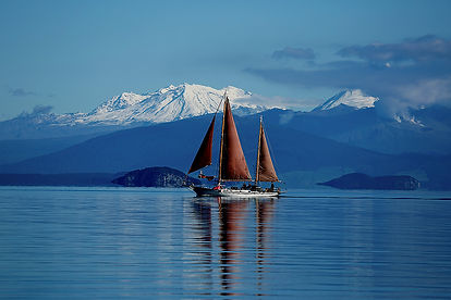 Sailing Lake Taupo with mountain peaks o