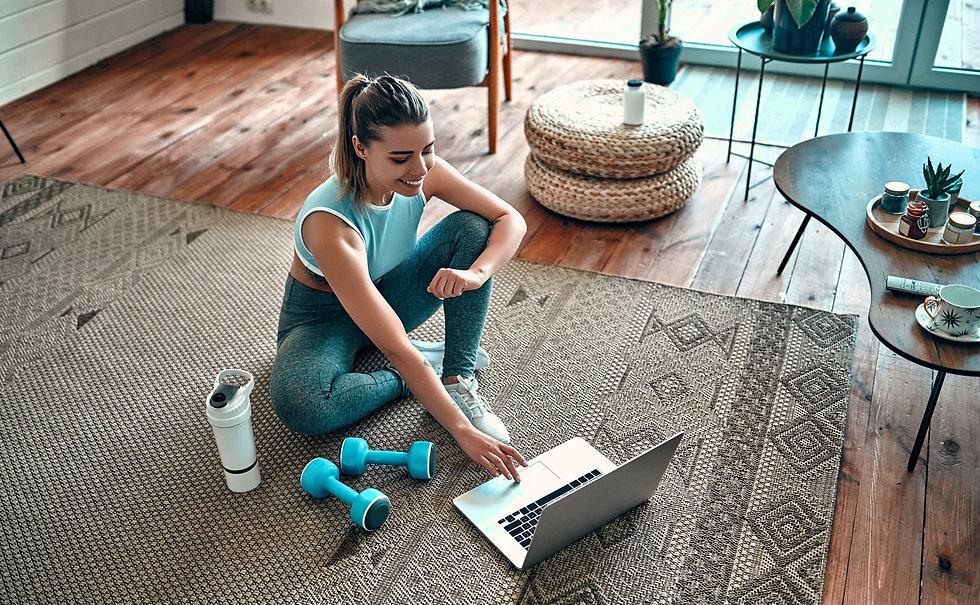 A sporty woman in sportswear is sitting