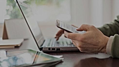 Homme devant un ordinateur portable et avec un téléphone dans la main