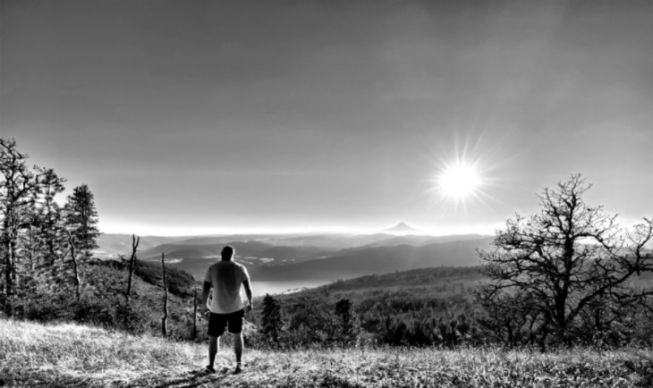 A man standing on a mountain trail watching the sun