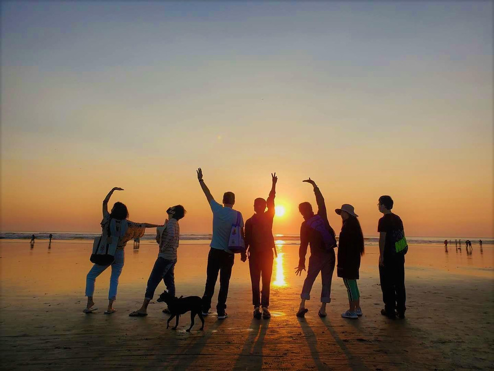 People are standing in front of the beach sunset