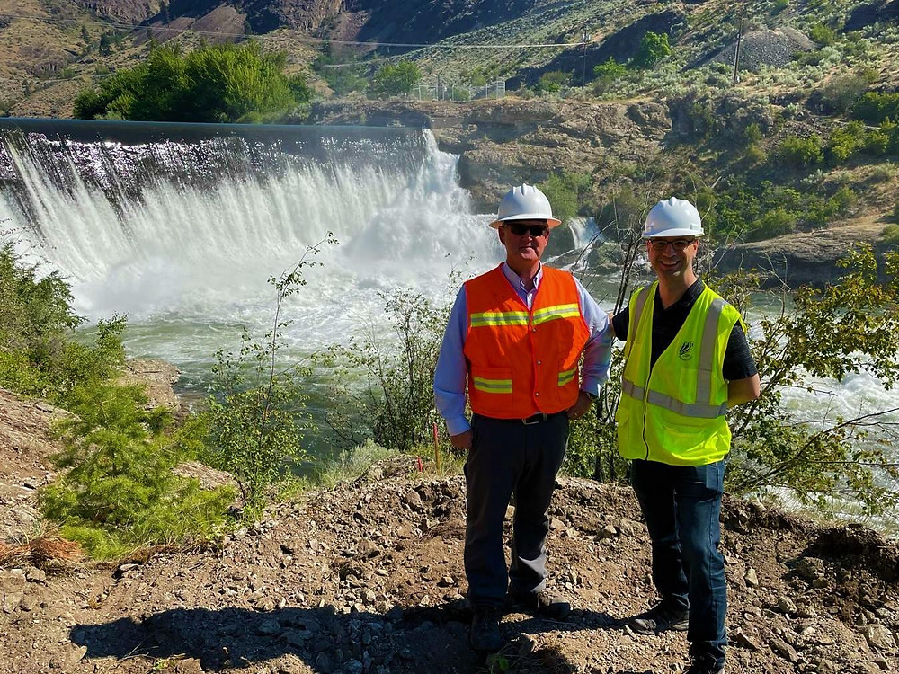 Two men are standing in front of the dam