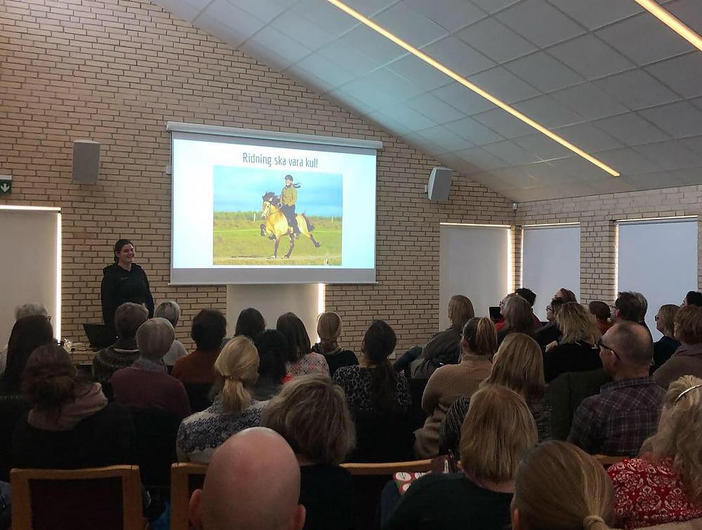 """Elin Bössfall håller föreläsning med temat Hästens välmående i träning, på powerpointbilden står """"Ridning ska vara kul!"""""""