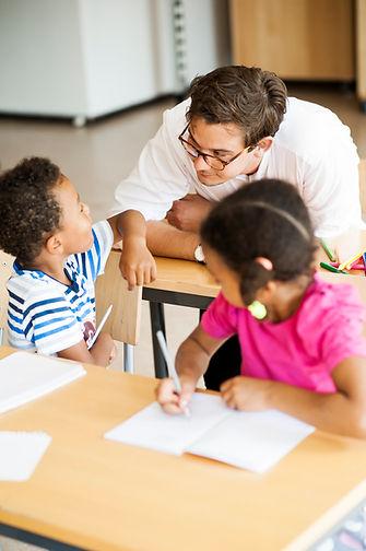 Boy-talking-with-teacher-in-classroom-DL