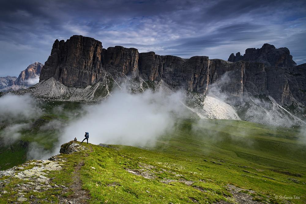Le nuvole salgono dalla valle mentre un escursionista ammira i Lastoi di Forminn