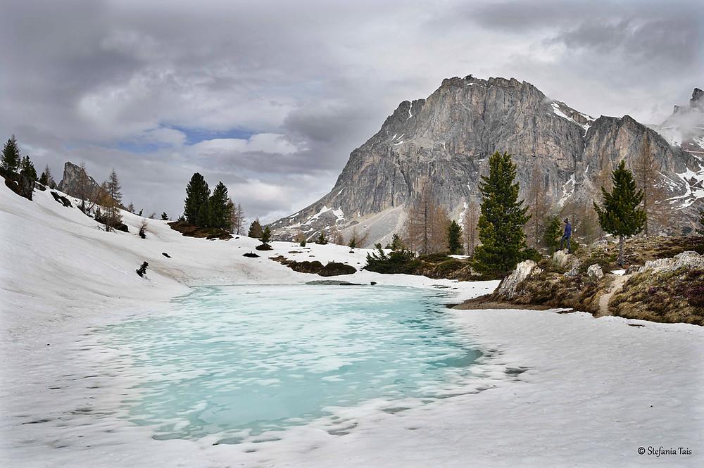 Il lago di Limedes al disgelo, la parete sud del Lagazuoi