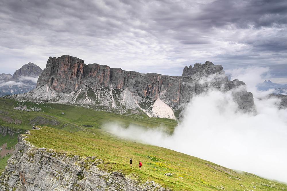 Escursionisti scendono verso i prati di Mondeval, di fronte i Lastoi di Formin
