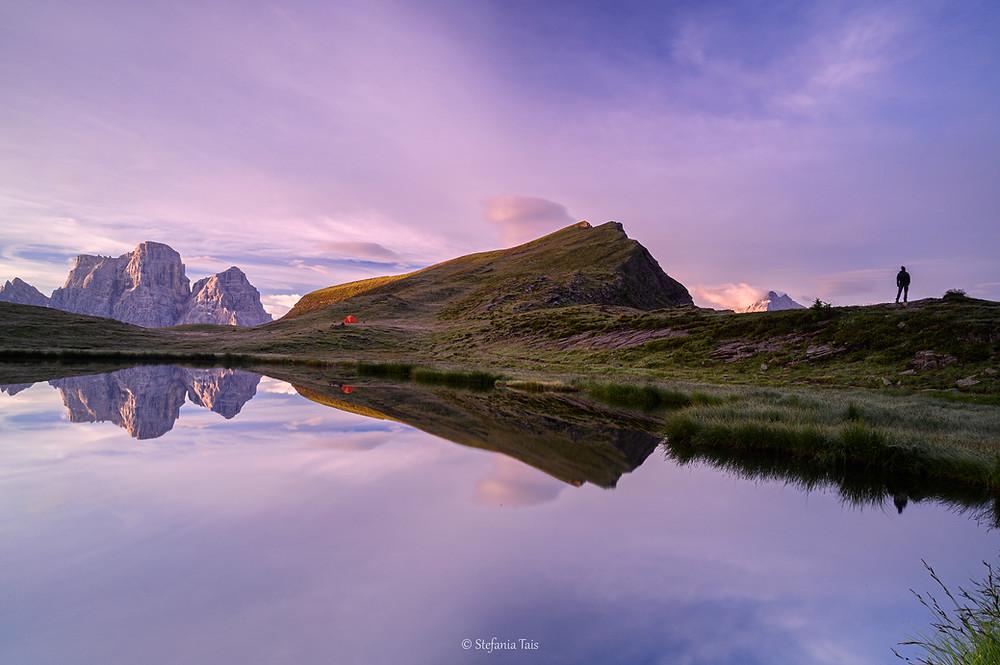 Escursionista all'alba presso il lago delle Baste, Pelmo e Corvo Alto di Mondeval si specchinano