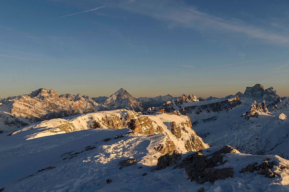 La calda luce del tramonto abbraccia il rifugio Lagazuoi, nello sfondo Sorapis, Antelao e Pelmo