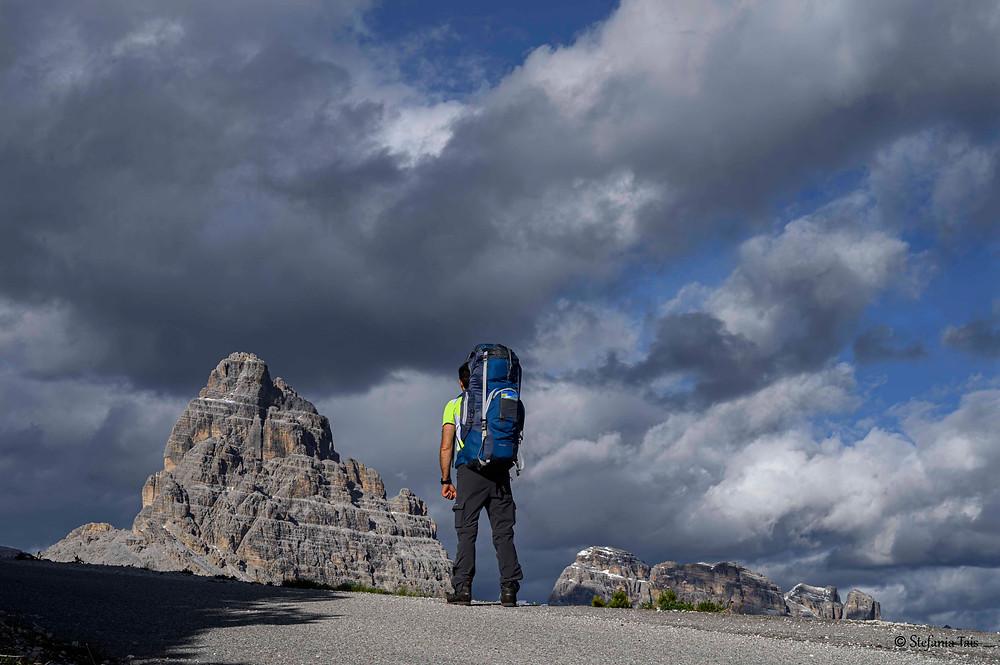 escursionista sul sentiero per il Monte Piana, in vista della Cima Ovest e del versante ovest della Cima Dodici