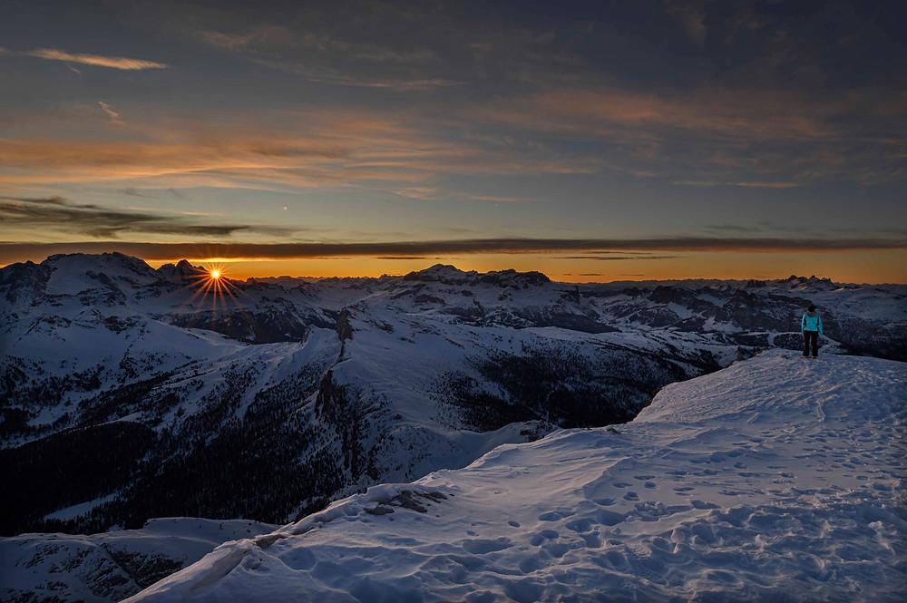 Il sole tramonta dietro il Padon, a sinistra la Marmolada, al centro il Gruppo del Sella