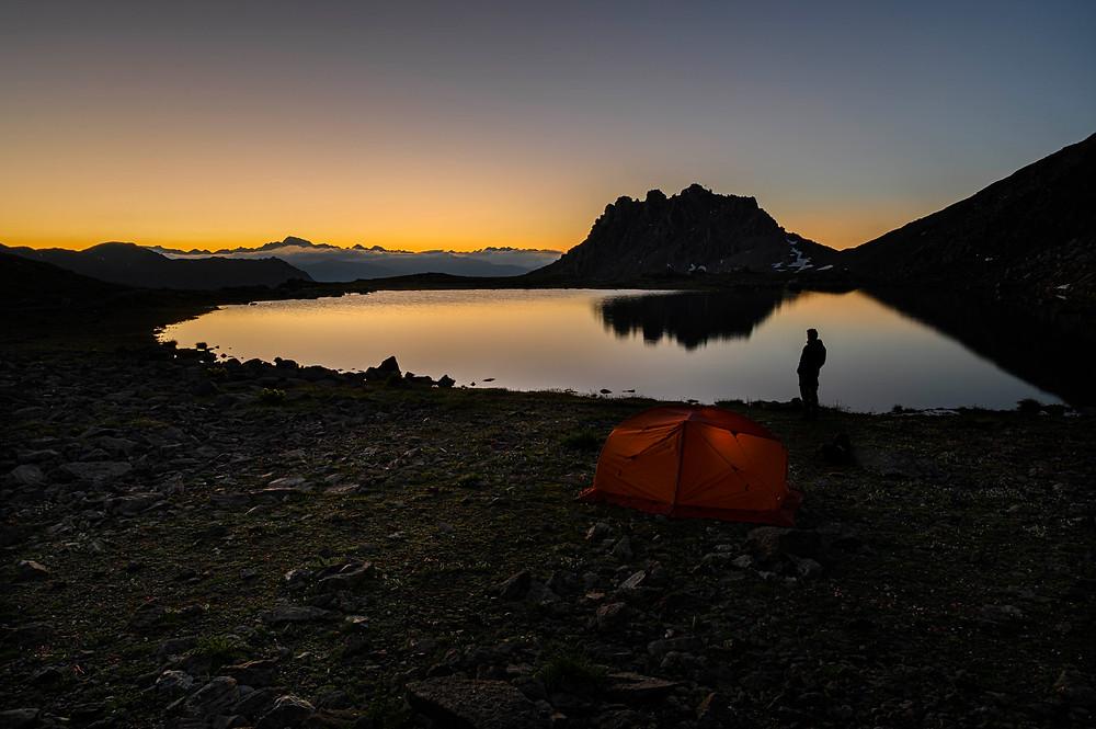 Escursionista sulle rive del Furkel see all'alba