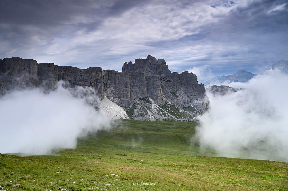 Nuvole salgono dalla valle sui prati di Mondeval