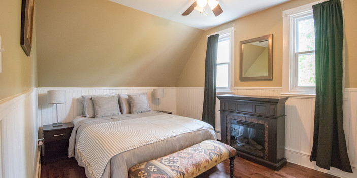 Master bedroom with queen bed and electric fire place.